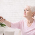 signora anziana telecomando udito tv